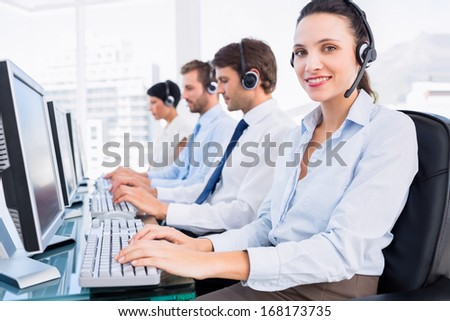 Side view of a group of business colleagues with headsets using computers at office desk - stock photo