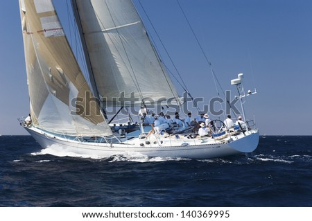 Side view of a group of crew members sitting on the side of a sailboat in the ocean against sky - stock photo