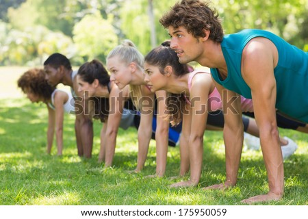 Side view of a group of fitness people doing push ups in the park - stock photo