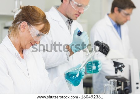 Side view of a group of scientists working in the laboratory - stock photo