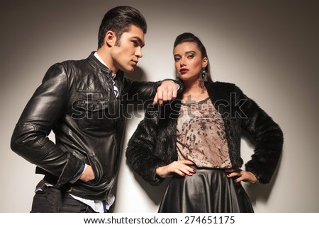 Side view of a handsome fashion man leaning on his girlfriend while holding his hands in pockets. - stock photo