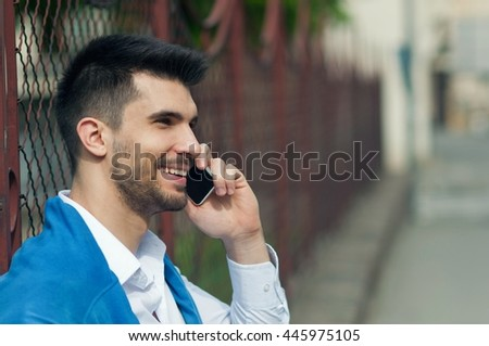 Side view of a handsome man talking on mobile phone