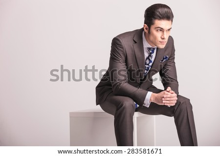Side view of a handsome young business man sitting on a white modern chair, holding his hands together. - stock photo