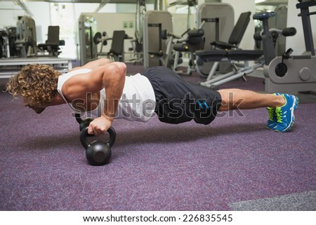 Side view of a handsome young man doing push ups with kettle bells in gym - stock photo