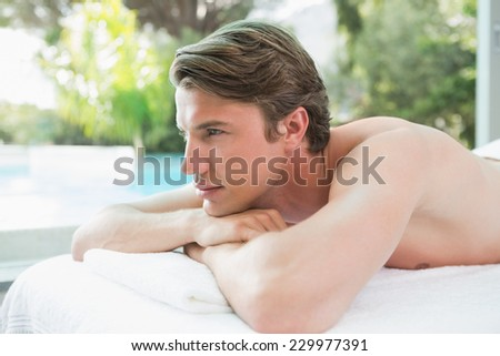 Side view of a handsome young man lying on massage table at spa center - stock photo