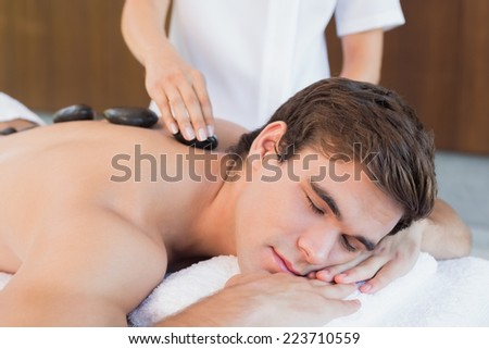 Side view of a handsome young man receiving stone massage at spa center - stock photo