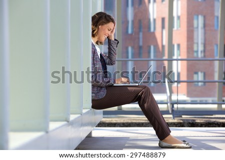 Side view of a happy business woman sitting outside using laptop - stock photo