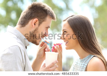 Side view of a happy couple falling in love and sharing a drink