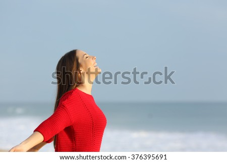 Side view of a happy excited woman wearing red sweater breathing fresh air on the beach with the horizon in the background - stock photo