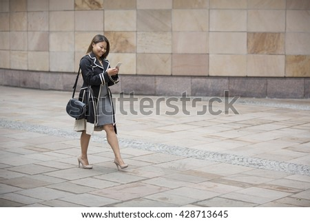 Side view of a happy Filipino Businesswoman walking on city street using a smart phone.