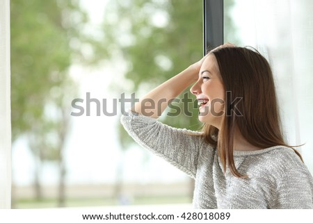 Side view of a happy girl laughing with hand on head and looking outdoors through a window at home or hotel room with a green background - stock photo