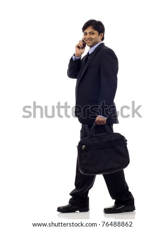Side view of a happy Indian business man walking, and he's talking on the mobile phone isolated over white background