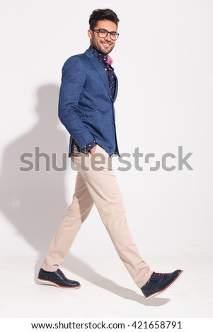 side view of a happy walking businessman looking at the camera in studio - stock photo