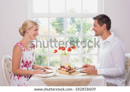 Side view of a happy young couple enjoying food at home - stock photo