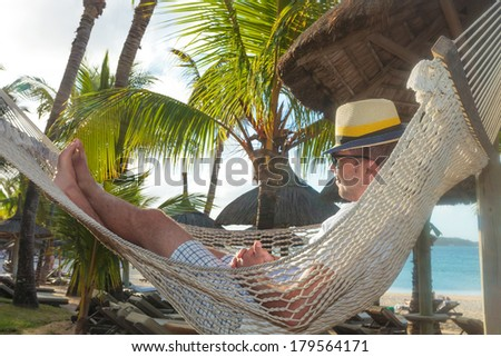 side view of a happy young man resting in a hammock on the beach, he looks away - stock photo