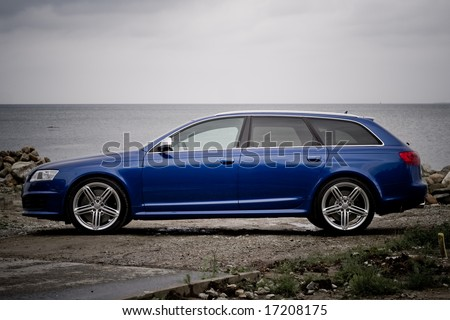 Side view of a high performance family estate car on a seashore