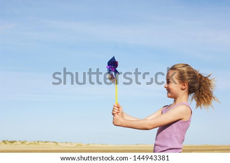 Side view of a little girl standing on windy beach with pinwheel against sky - stock photo