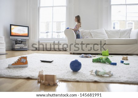 Side view of a little girl watching television with toys on floor in foreground - stock photo