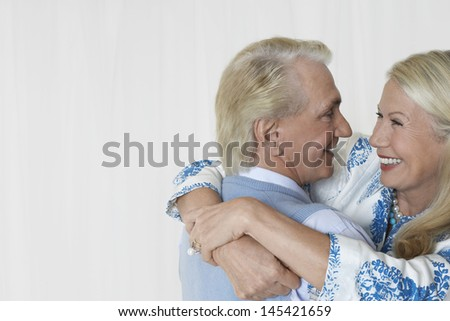 Side view of a loving and happy senior couple embracing against white background - stock photo