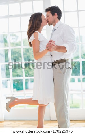 Side view of a loving young couple kissing at home - stock photo