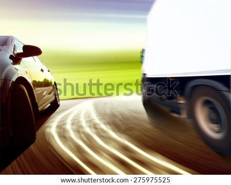 Side view of a luxury car driving fast on a winding road in the woods - stock photo