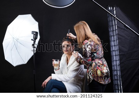 Side view of a make-up artist preparing female model for photo shoot