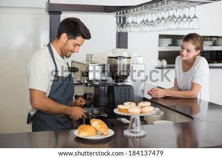 Side view of a male cafe owner with woman at the coffee shop