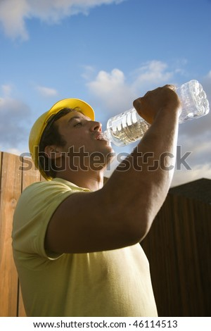 Side view of a male Caucasian construction worker as he drinks from a plastic water bottle. A fence and the blue sky can be seen in the background. Vertical shot.