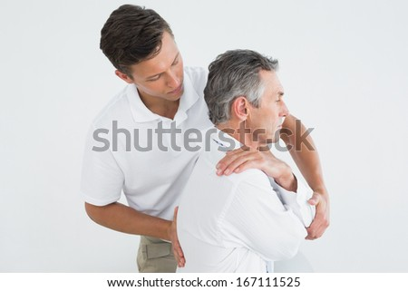 Side view of a male chiropractor examining mature man over white background - stock photo