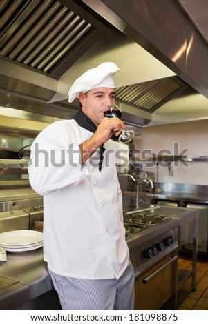 Side view of a male cook drinking red wine in the kitchen
