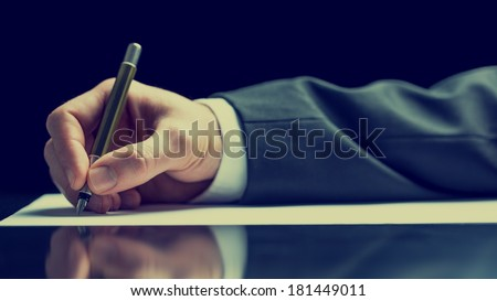 Side view of a male hand writing on a sheet of white paper with a fountain pen, vintage effect toned image. - stock photo