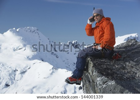 Side view of a male mountain climber using walkie talkie against mountain peak - stock photo