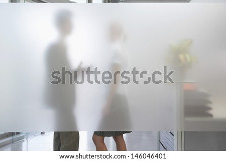 Side view of a male office worker talking to female colleague behind translucent wall in office - stock photo