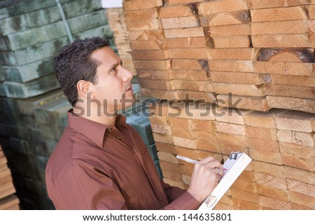 Side view of a male supervisor stock taking in warehouse - stock photo