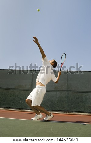 Side view of a male tennis player serving ball on court - stock photo