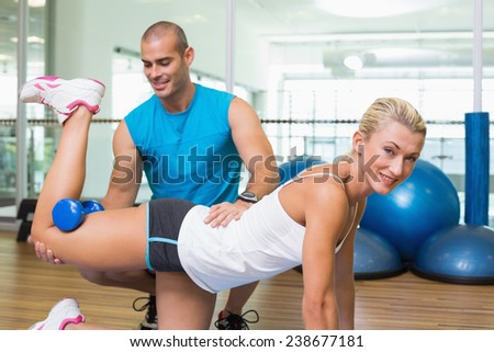 Side view of a male trainer assisting woman with exercises at fitness studio - stock photo