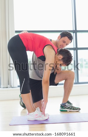 Side view of a male trainer assisting young woman with stretching exercises in the fitness studio - stock photo