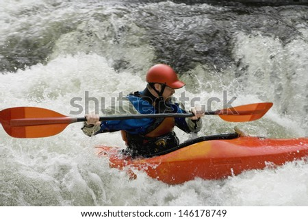 Side view of a man kayaking in rough river - stock photo