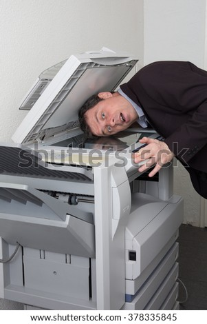 Side view of a man putting his head in copy machine