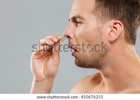 Side view of a man removing nose hair with tweezers isolated on the gray background