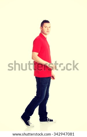 Side view of a man walking forward. - stock photo