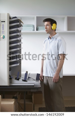Side view of a man with headphones standing by photocopier in office - stock photo