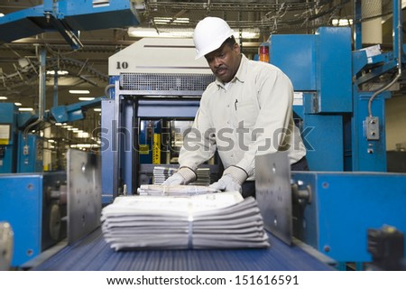 Side view of a man working on newspaper production line in newspaper factory - stock photo
