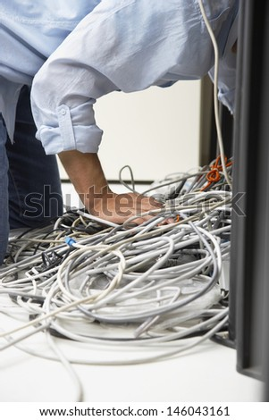 Side view of a man working on tangled computer wires in office - stock photo