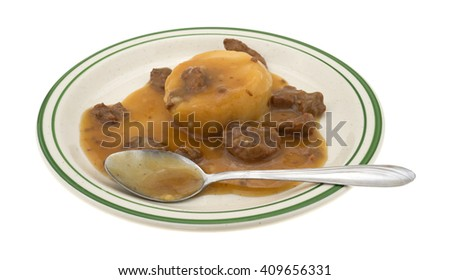 Side view of a mashed potatoes in gravy with beef tips TV dinner on a green striped plate with a spoon isolated on a white background. - stock photo