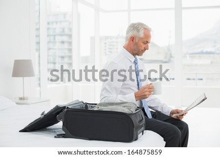 Side view of a mature businessman with coffee cup reading newspaper by luggage at a hotel room - stock photo