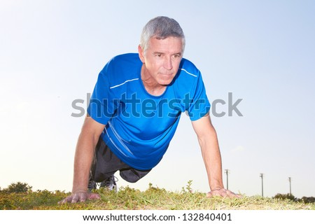 Side view of a mature man in sportswear doing push ups on ground against clear sky. Horizontal shot. - stock photo