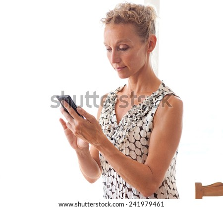 Side view of a mature professional business woman using a smartphone device while sitting on her office desk with white space. Business and lifestyle technology, interior. - stock photo