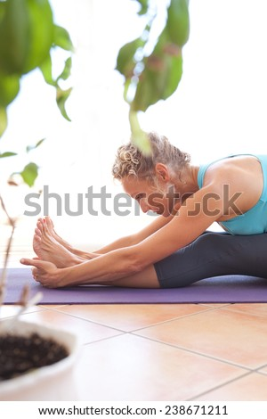 Side view of a mature professional woman exercising and stretching her body doing flexibility exercises and bending her back, sitting on a yoga mat indoors. Senior woman fit and healthy lifestyle. - stock photo