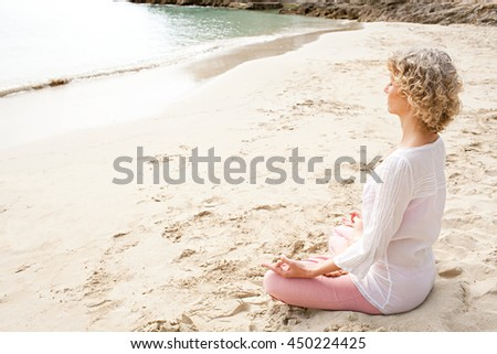 Side view of a mature woman in holiday destination beach contemplating the sea sitting on shore in yoga position, meditating outdoors. Well being mature sport and healthy lifestyle, nature exterior. - stock photo